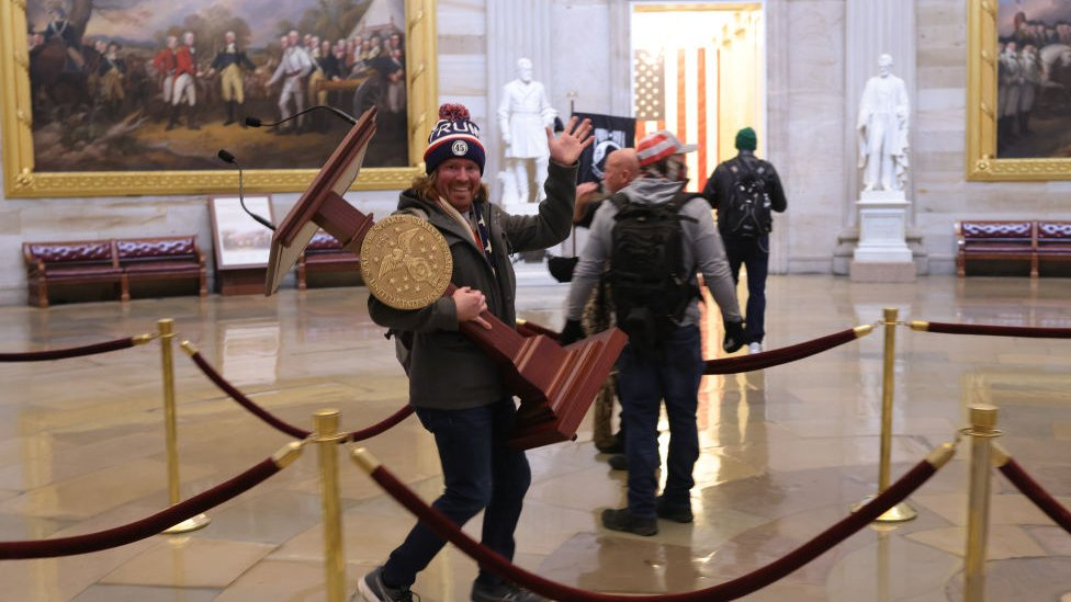 One protester carries a plinth from a room in the US Capitol