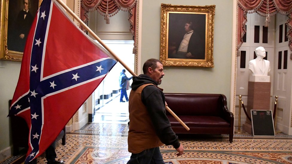 A protester carries the Confederate flag into the US Capitol building