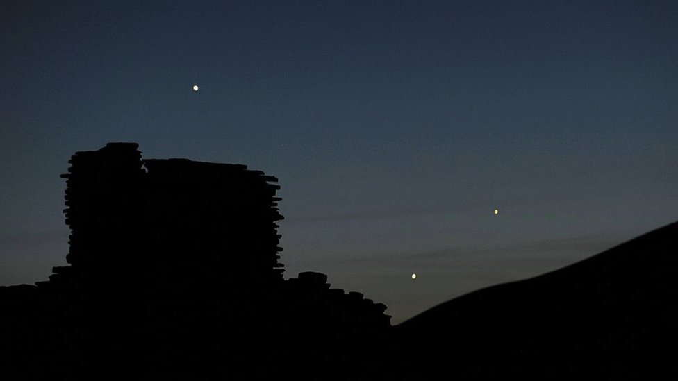The planets Jupiter (L), Venus (C) and Mercury (R) are seen in an unusual conjunction.