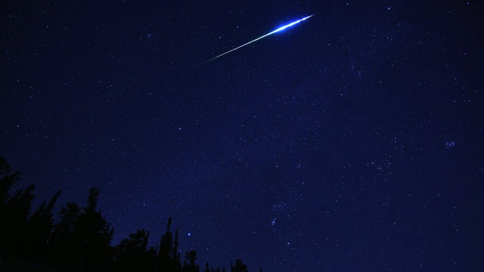A blue/green glowing meteor crosses the sky. Dark forest visible in the horizon.