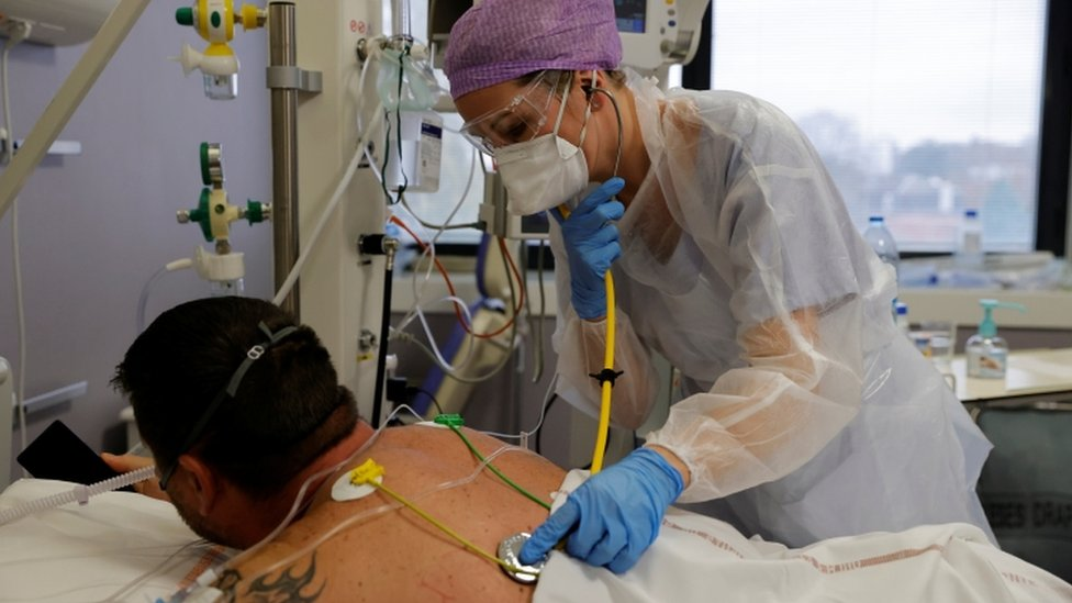 A doctor wearing a protective suit and a face mask, examines a patient in the intensive care unit in France
