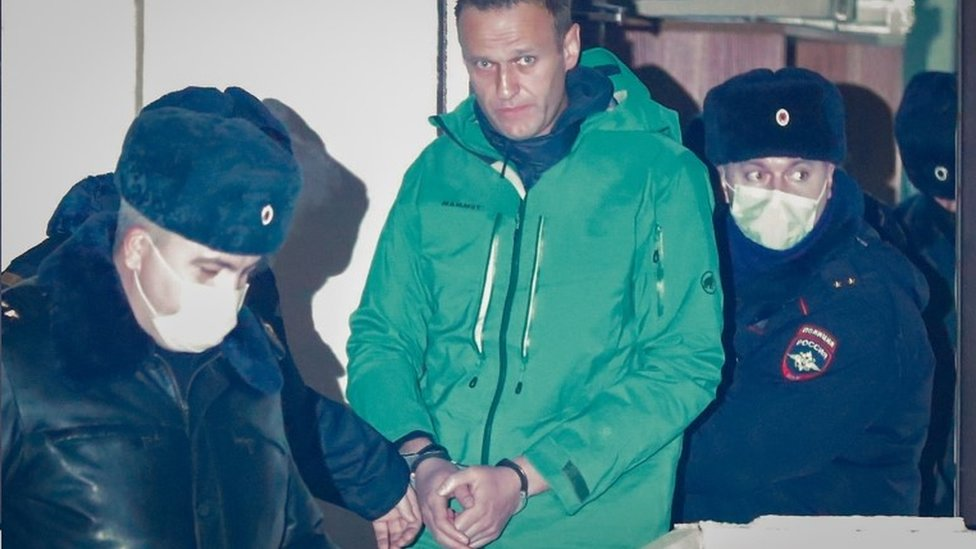 Alexei Navalny (centre) is escorted by police in Khimki, outside Moscow, Russia. Photo: 18 January 2021