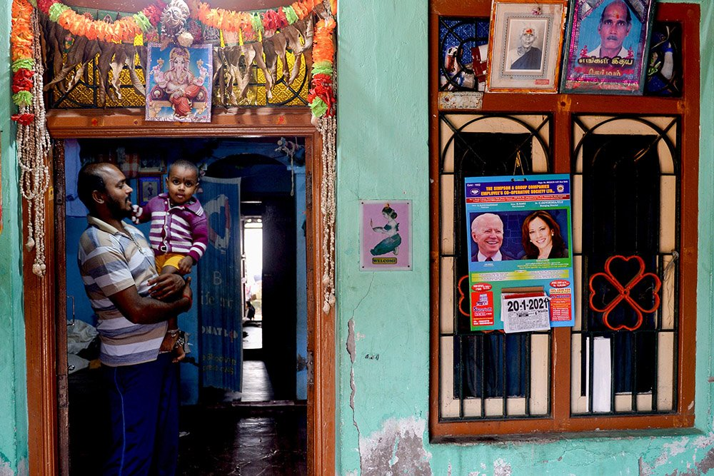 A man stands in this house decorated with a calendar with photos of US President-elect Joe Biden and Vice President-elect Kamala Harris
