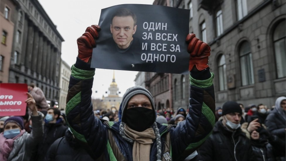 """A protester holds a poster that reads """"One for all and all for one"""", during an unauthorized protest in support of Russian opposition leader and blogger Alexei Navalny"""