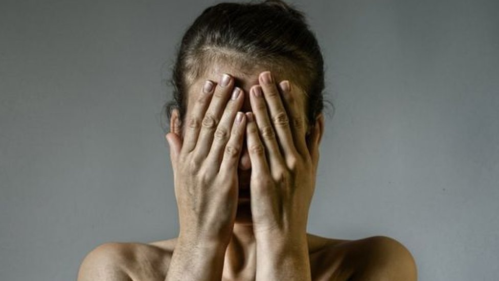 Žena pokriva lice rukama