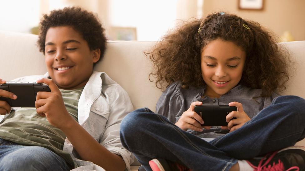 Siblings playing on their phones