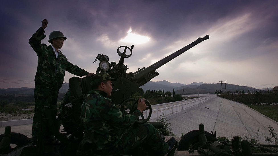 Chinese workers operate a cloud seeding cannon