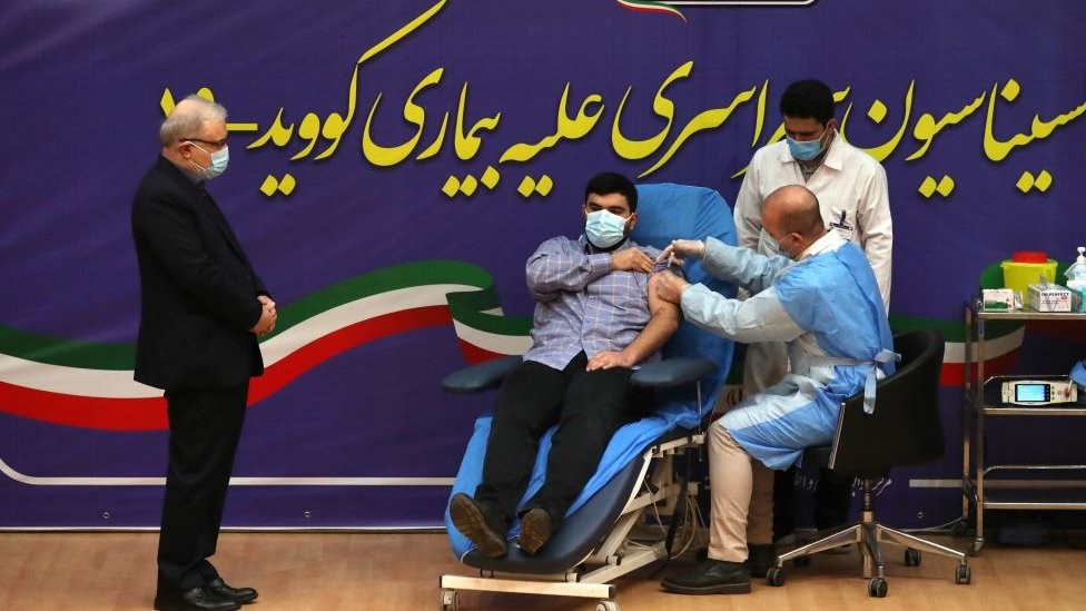 Iranian Health Minister Saeed Namaki (L) watches while his son Parsa receives the first Covid-19 vaccine