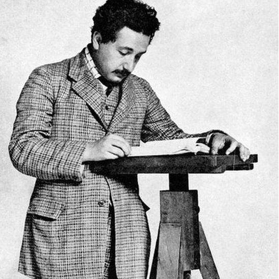 Black and white photo of Albert Einstein reading a book. He is believed to be 26 years old in this picture.