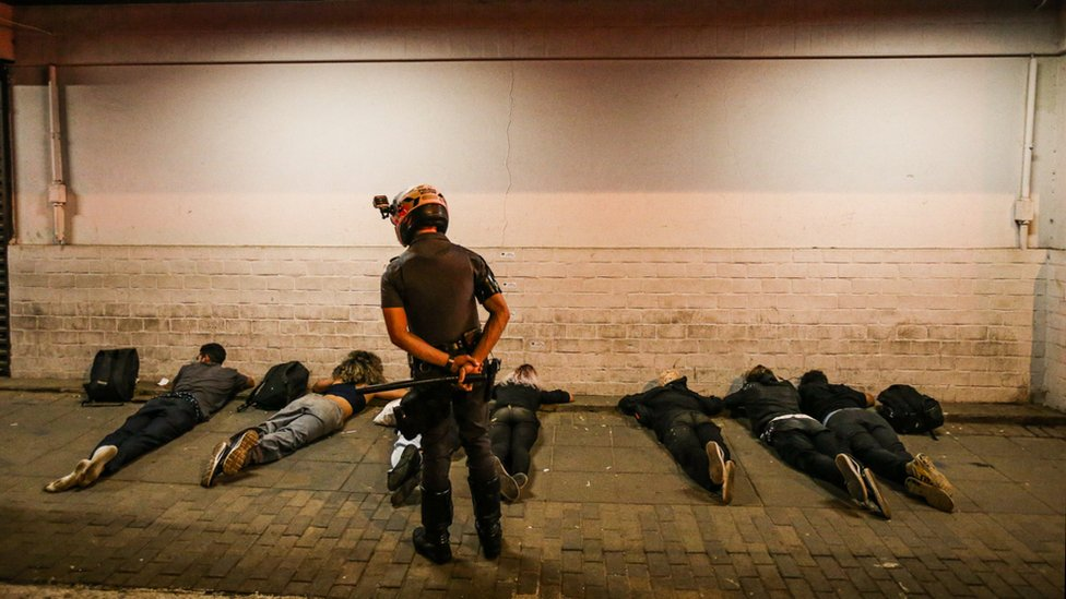 Seven BLM protesters lie on the ground as a policeman stands over them