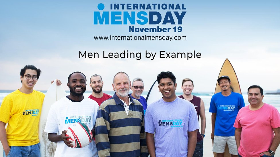 International Men's Day poster for 2018 - a group of men stand smiling on the beach under tag line Men Leading By Example