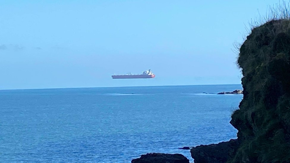 Hovering ship photographed off the coast of Cornwall