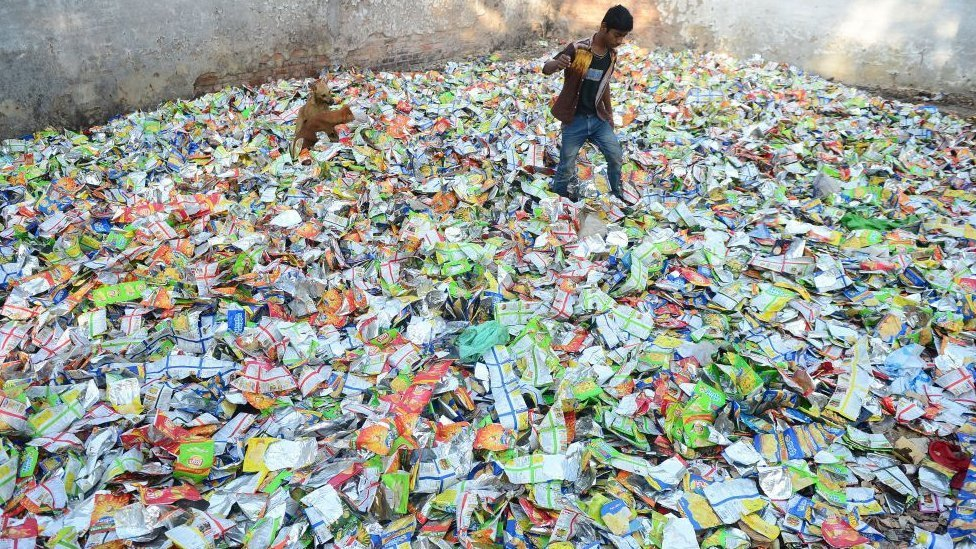 A boy searches for food in polythene packets at a roadside in India
