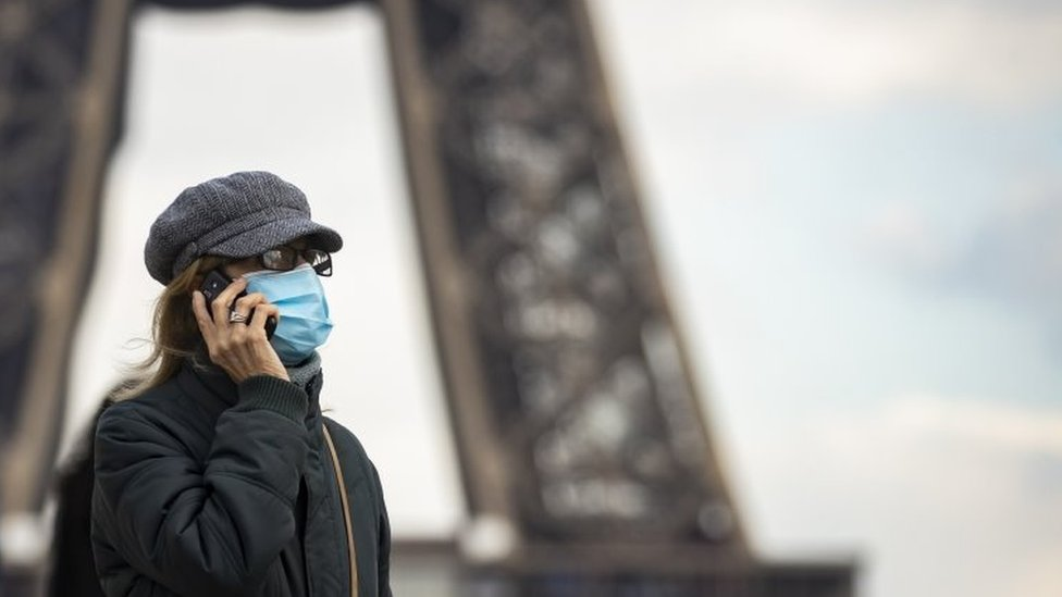 A woman wearing a surgical face mask walks near the Eiffel Tower