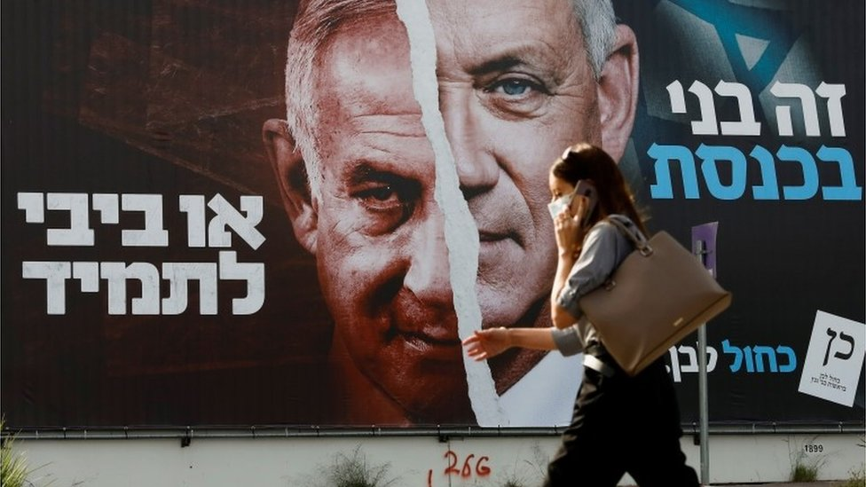 Woman walks past Israel election campaign poster in Tel Aviv (14/03/21)