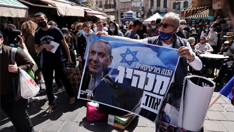 Man holds up pro-Netanyahu poster in Jerusalem (21/03/21)