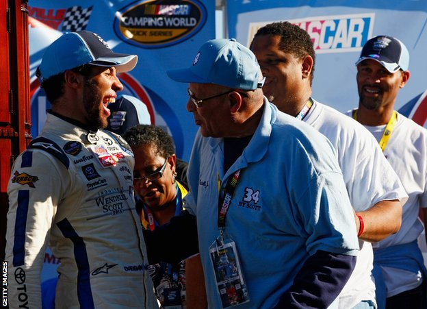 Wendell Scott Jr congratulates Bubba Wallace on a 2013 victory, with Warrick also present
