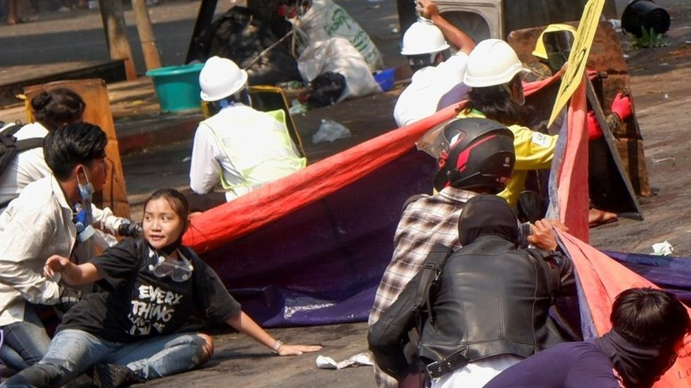 Protesters lie on the ground after police opened fire to disperse an anti-coup protest in Mandalay