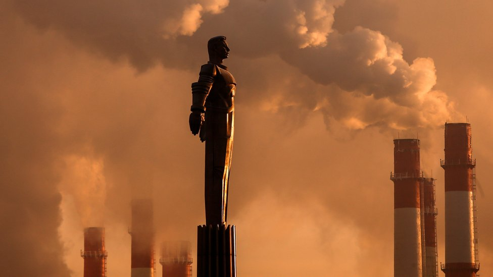 Steam rising from chimneys plant near a monument of Yuri Gagarin, during sunset in Moscow