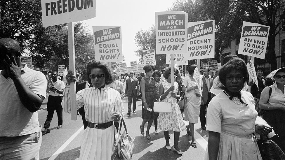 Civil rights march on Washington, DC, USA. Procession of African Americans carrying placards demanding equal rights, integrated schools, decent housing, and an end to bias