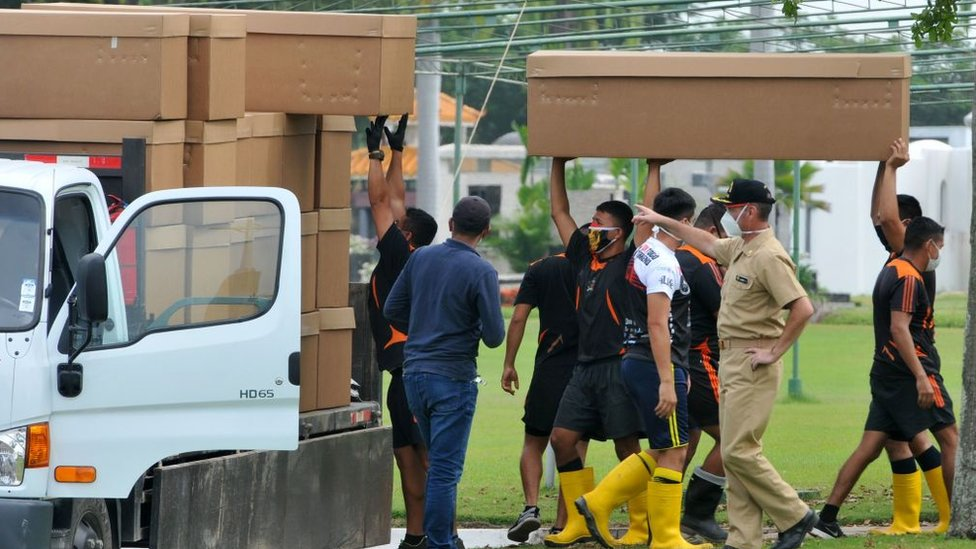 Soldiers in Ecuador pilling cardboard coffins on a lorry.