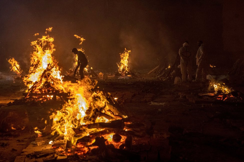 Workers and relatives stand around burning funeral pyres at night