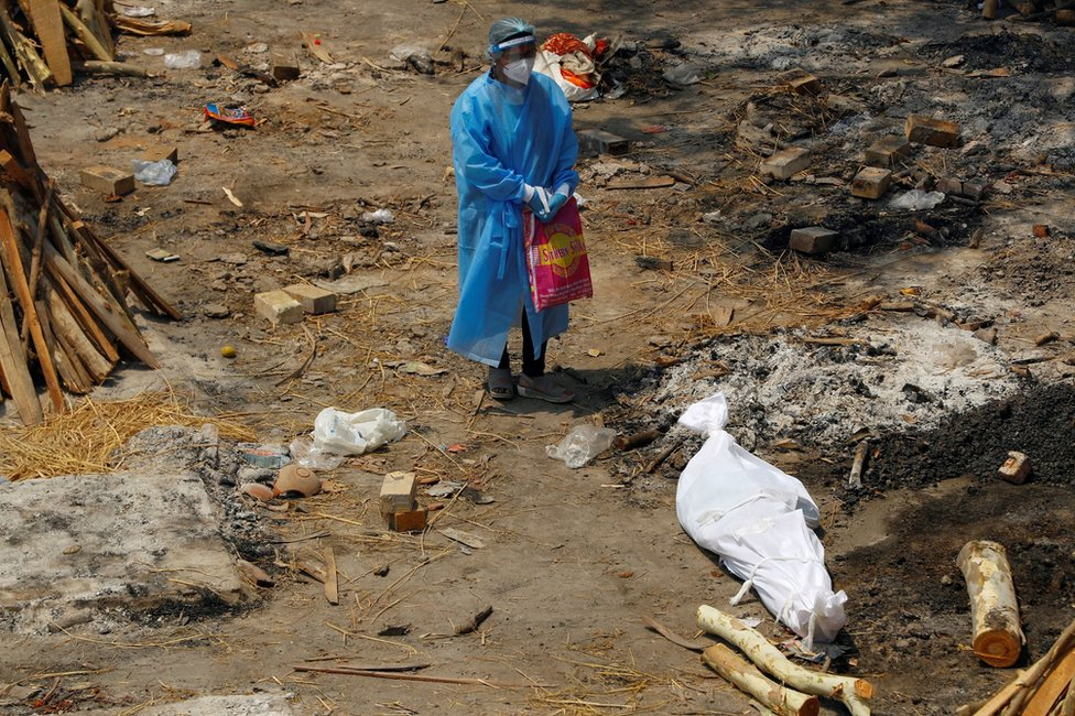A woman wearing PPE stands next to the body of a family member in New Delhi, India