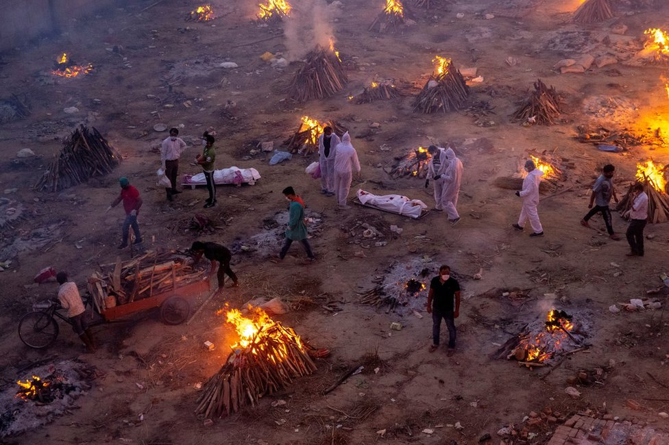 People wait to cremate Covid victims whilst surrounded by burning funeral pyres in New Delhi, India
