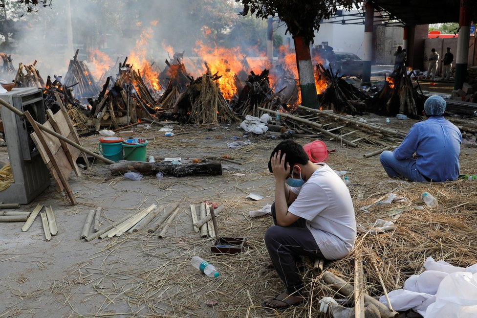Family members sit next to the burning funeral pyres in New Delhi, India