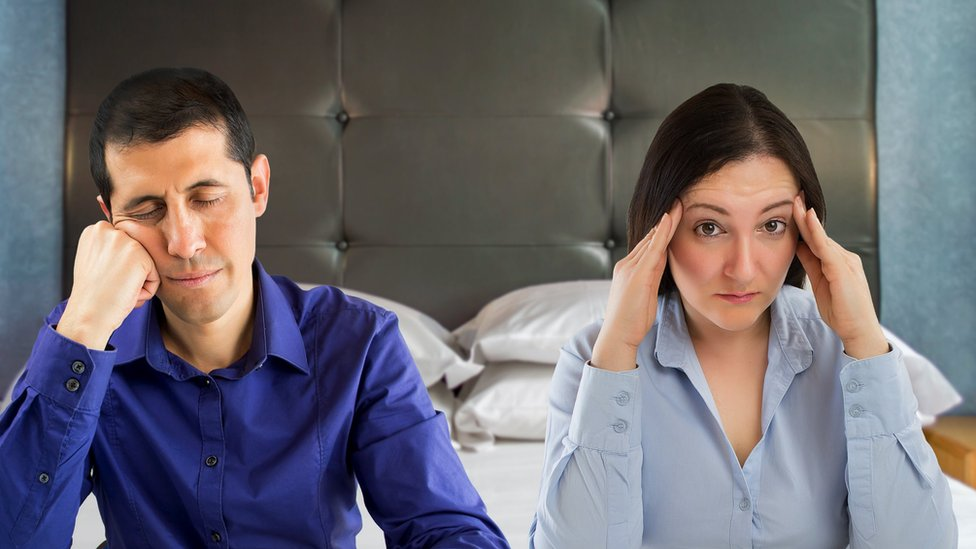 A worried woman and a bored man sitting on their bed.