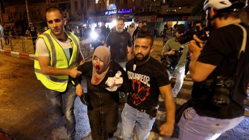An injured Palestinian woman is led to safety in Jerusalem. Photo: 8 May 2021