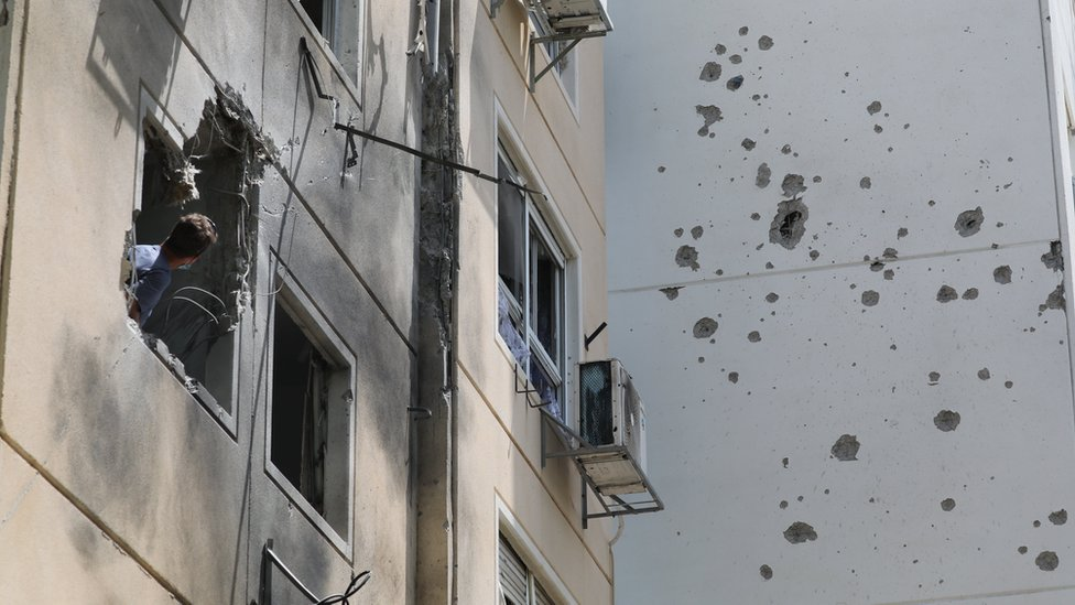 A man looks at the damage caused by a Palestinian rocket that hit a block of flats in the southern Israeli city of Ashkelon (11 May 2021)