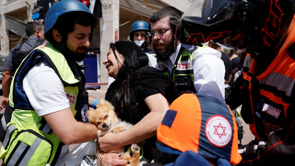Israeli medics help a woman after a rocket hit a shopping centre in Ashkelon, southern Israel (11 May 2021)