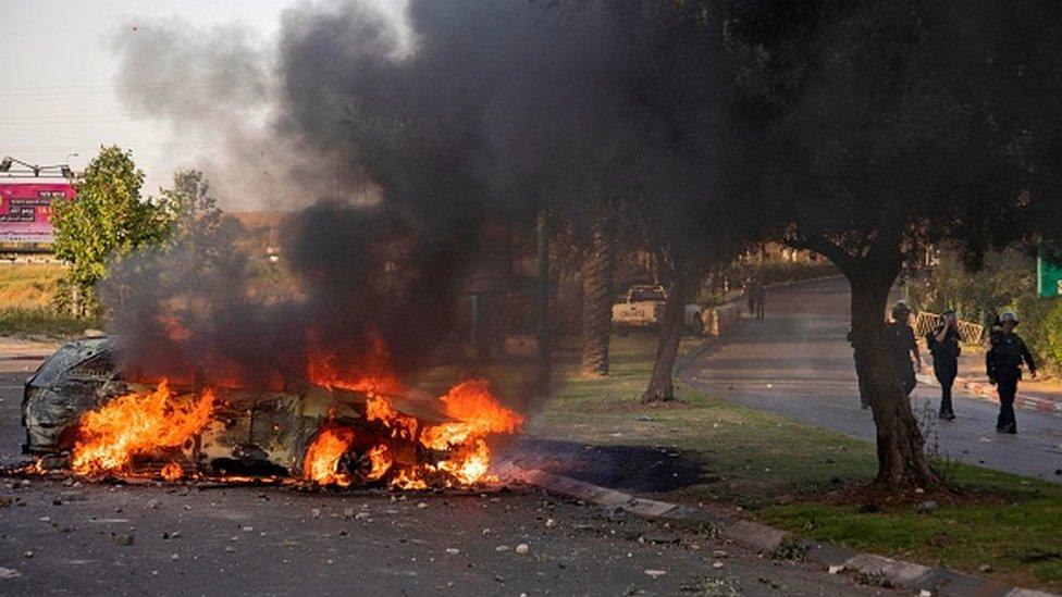 An Israeli police car burns after an Arab Israeli demonstration following a funeral in Lod near Tel Aviv