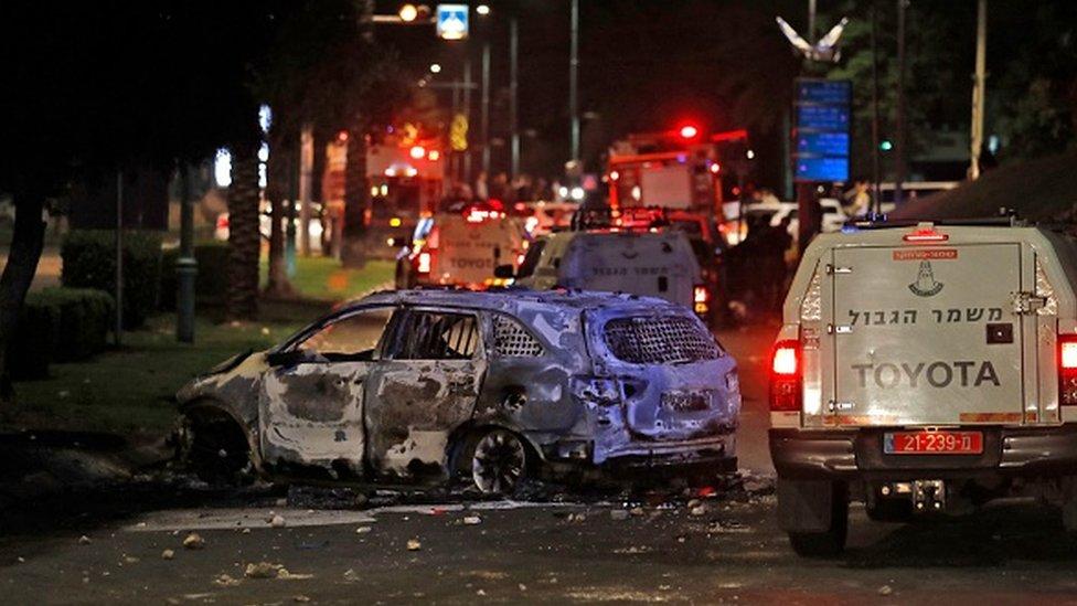 Israeli border police vehicles drive past an extinguished burnt vehicle in Lod near Tel Aviv
