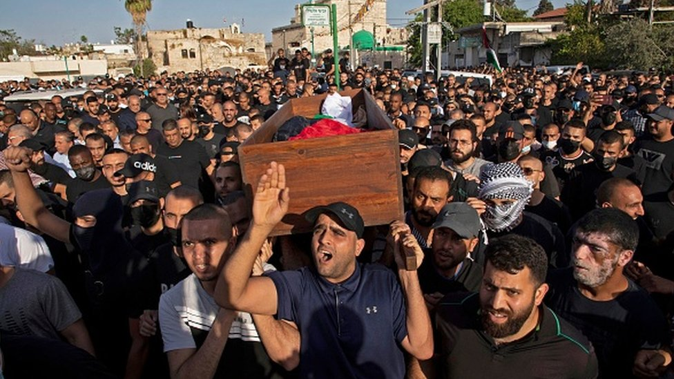 Arab Israelis gesture and wave Palestinian flags during a funeral in the central Israeli city of Lod near Tel Aviv
