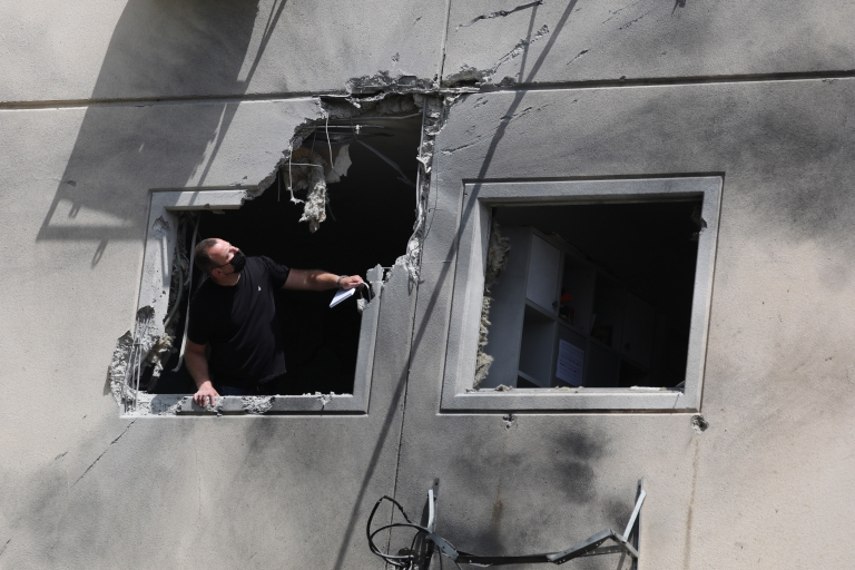 A man inspects damage on a building in the city of Ashkelon, Israel
