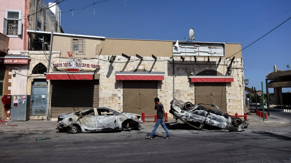 A man walks past two cars burnt during unrest in the Israeli city of Lod
