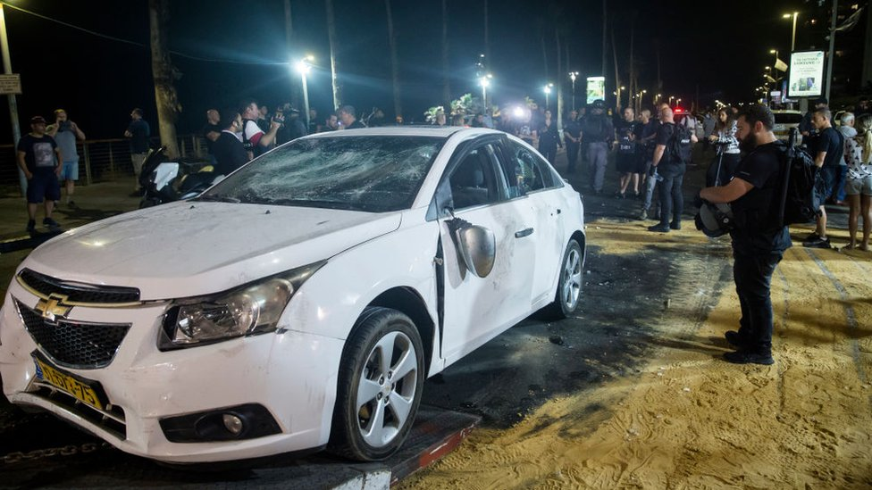 Police inspect damage to a car attacked by a Jewish mob on Wednesday night
