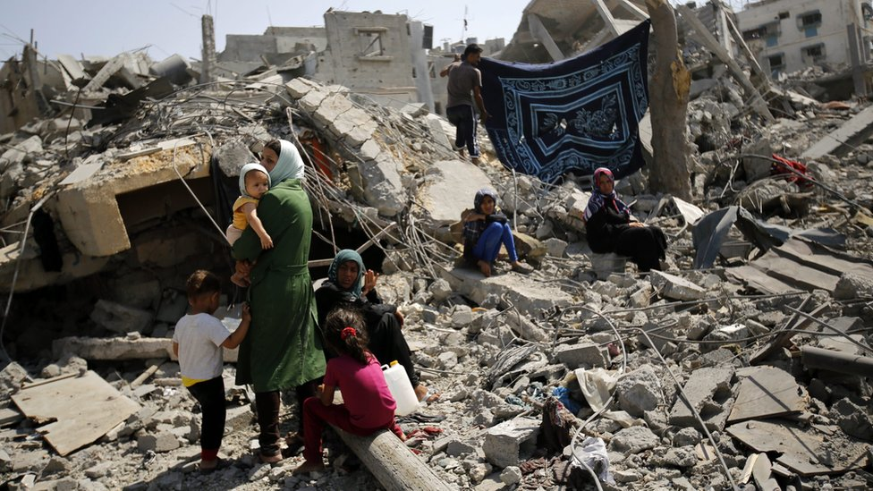 Members of the al-Kafarna family inspect the rubble of their destroyed house in Beit Hanoun, northern Gaza, on 1 August 2014