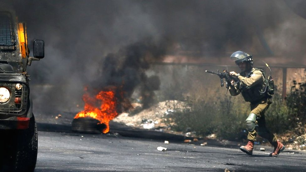 An Israeli soldier gets into position during clashes with Palestinian demonstrators in the West Bank