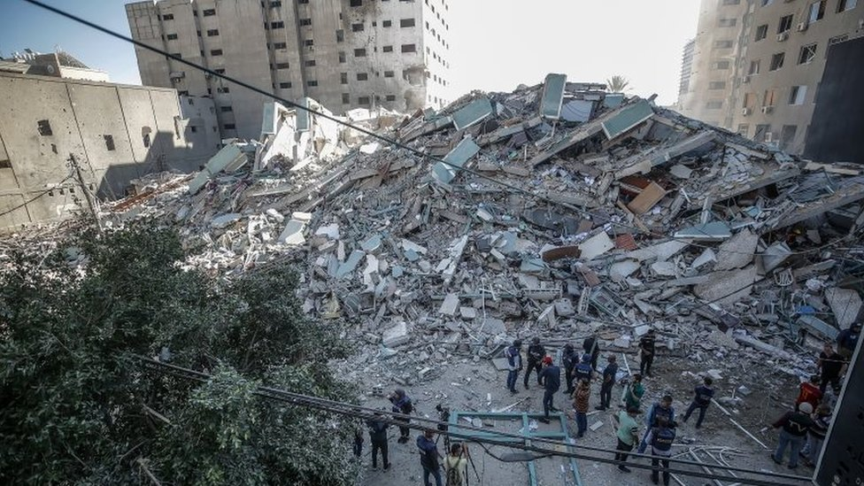 Palestinians inspect the rubbles after an Israeli air strike hit Al-Jalaa tower, which houses apartments and several media outlets, including the Associated Press and Al Jazeera, in Gaza City, 15 May 202