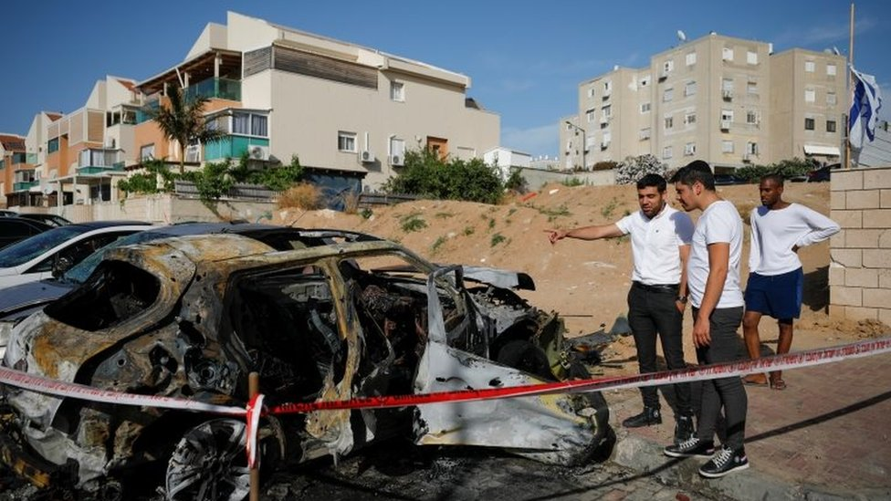 People look at a damaged car at a site where a rocket fired from Gaza landed, as Israeli-Palestinian cross-border violence continues, in Ashkelon, southern Israel, May 16, 2021