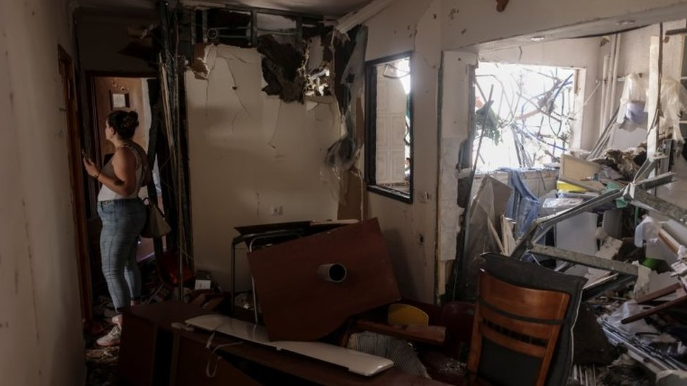 """A woman walks inside her parents"""" apartment after it was hit with a rocket fired from Gaza, in Ashdod, Israel"""