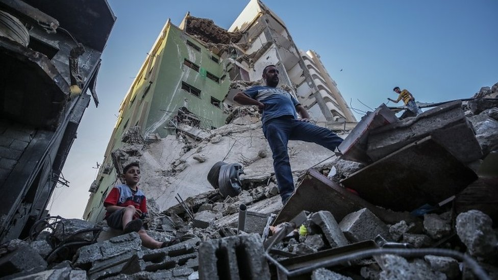 Palestinians inspect the rubble of their destroyed house after Israeli airstrikes