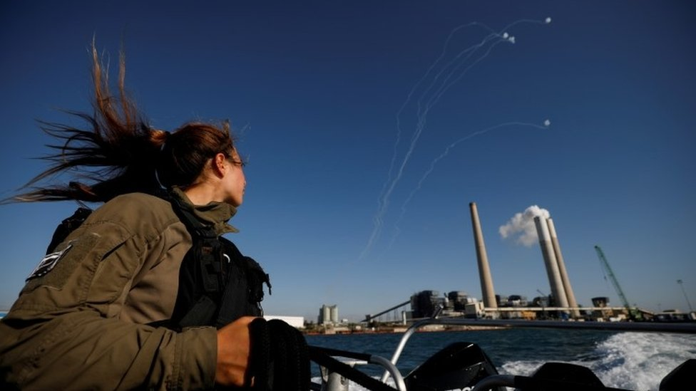An Israeli soldier looks on as Israel's Iron Dome anti-missile system intercept rockets launched from the Gaza Strip