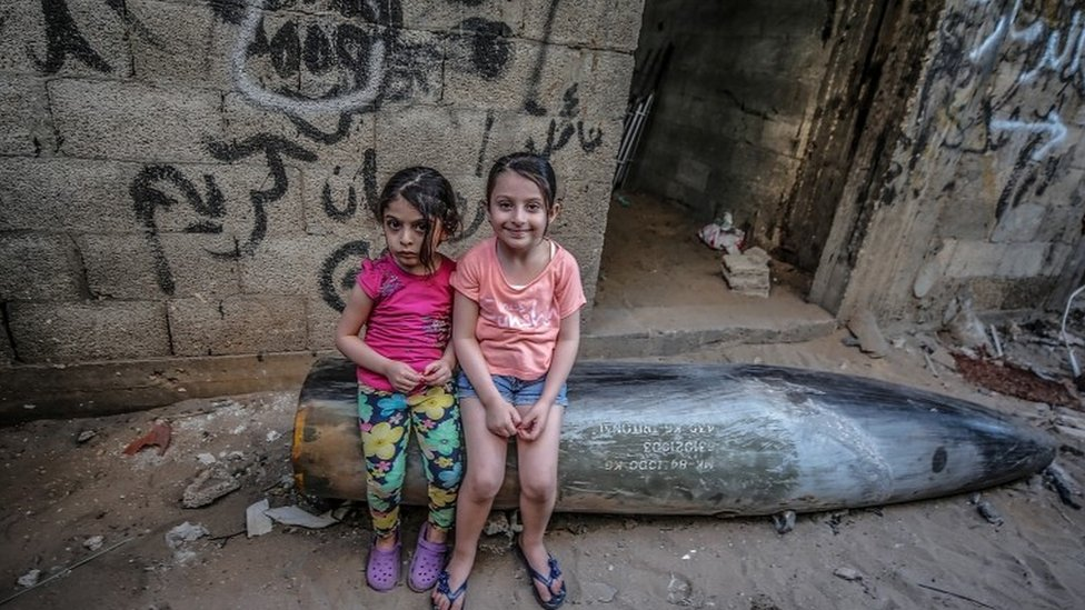 Palestinian sisters sit on an unexploded missile fired by Israeli warplanes in Gaza