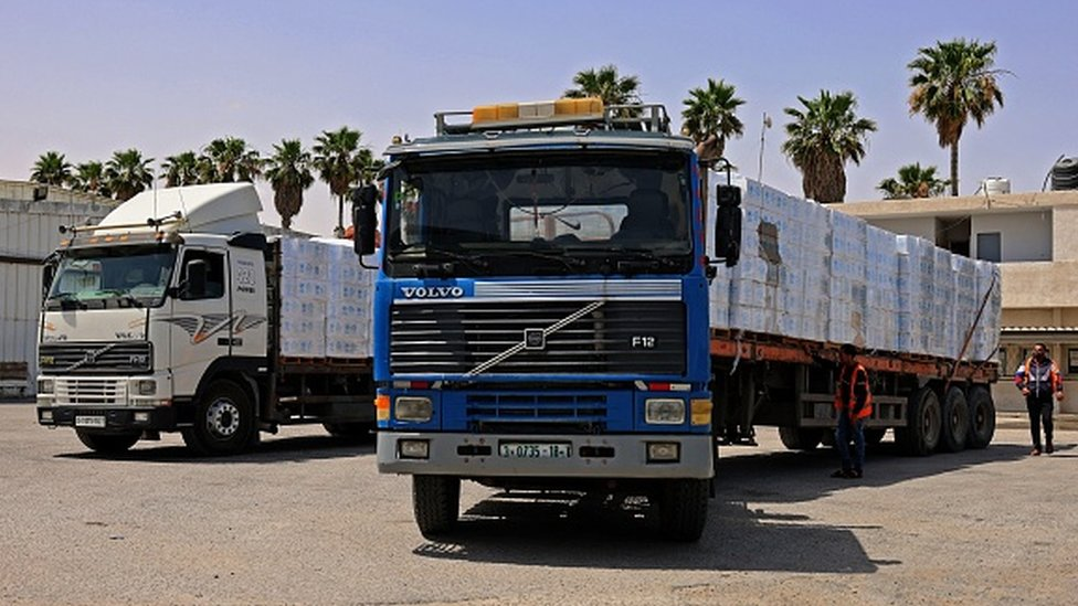 Trucks loaded with humanitarian aid pass into the Gaza Strip through the Kerem Shalom crossing