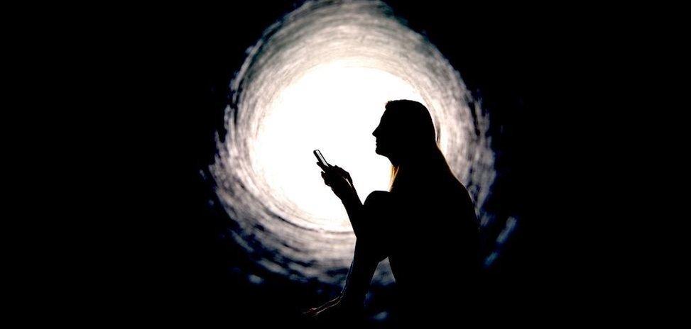 Žena u apstraktnom tunelu drži telefon u rukama