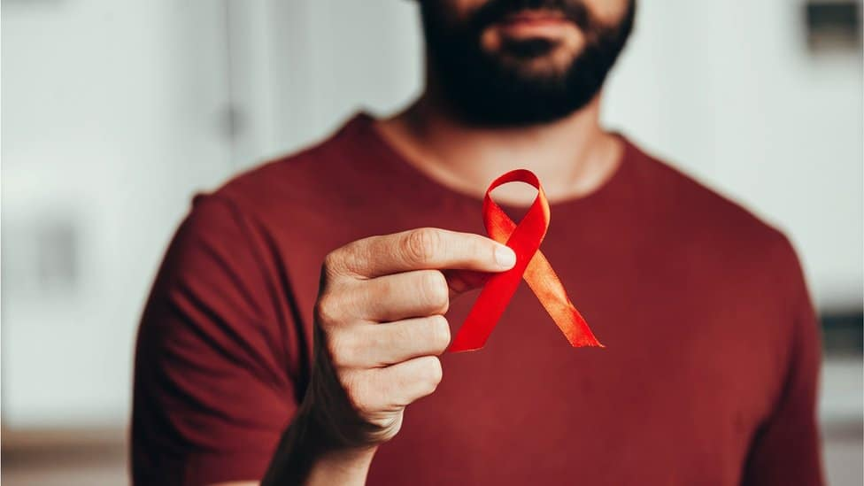 A man holding a red ribbon for HIV illness awareness (stock photo)